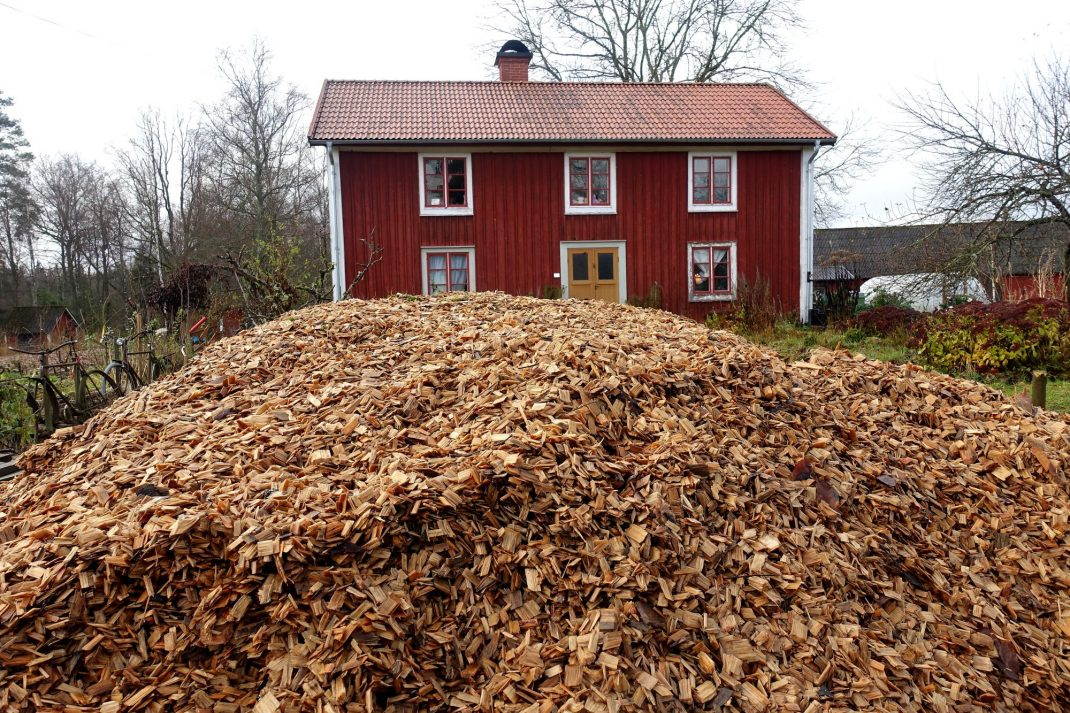 En hög med träflis på uppfarten framför huset. Wood chips outside the house.