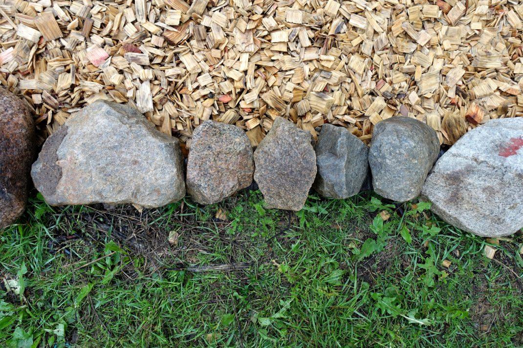 En kant av stora grå stenar i mitten av bilden, träflis i övre delen och gräs nedanför kanten. Edge your beds, a row of rocks edging my beds