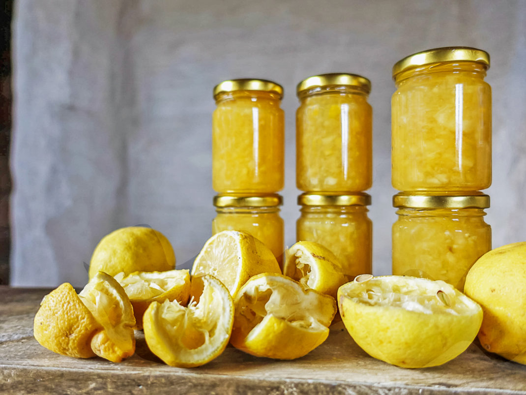Glasburkar med citronmarmelad och citroner. Glass jars with lemon marmalade.