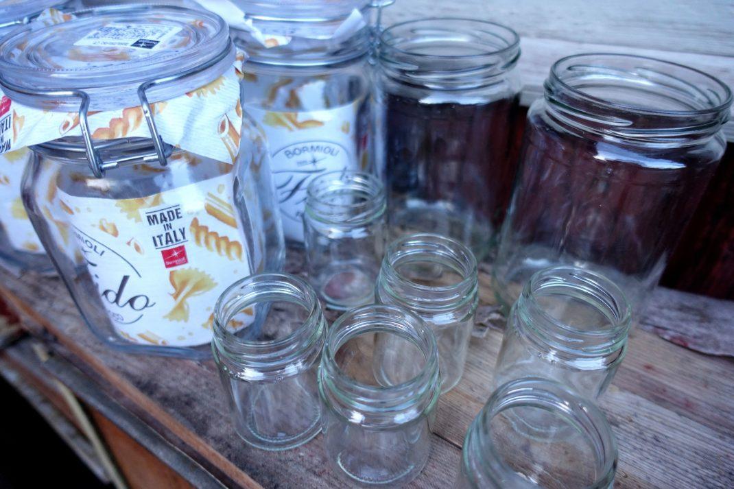 Glasburkar i olika storlekar står uppställda.