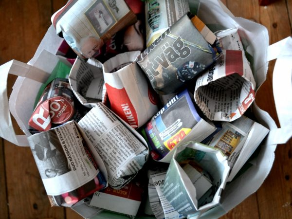 A paperboy filled with pots made from paper.