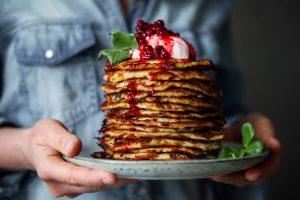 En hög med raggmunkar med klarröd lingonsylt på en tallrik. A pile of potatoes pancakes on a plate with red lingonberry jam on top.