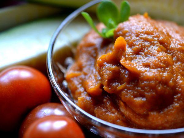 En skål med röd salsa står bredvid glansiga tomater inne i köket.