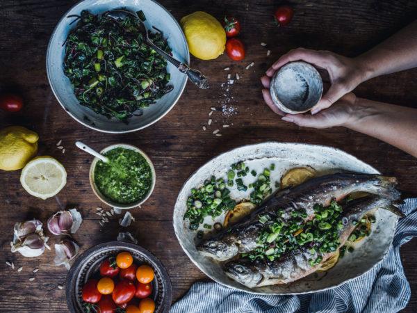 Ett bord med massor av gott; fisk, fräst mangold och andra tillbehör.
