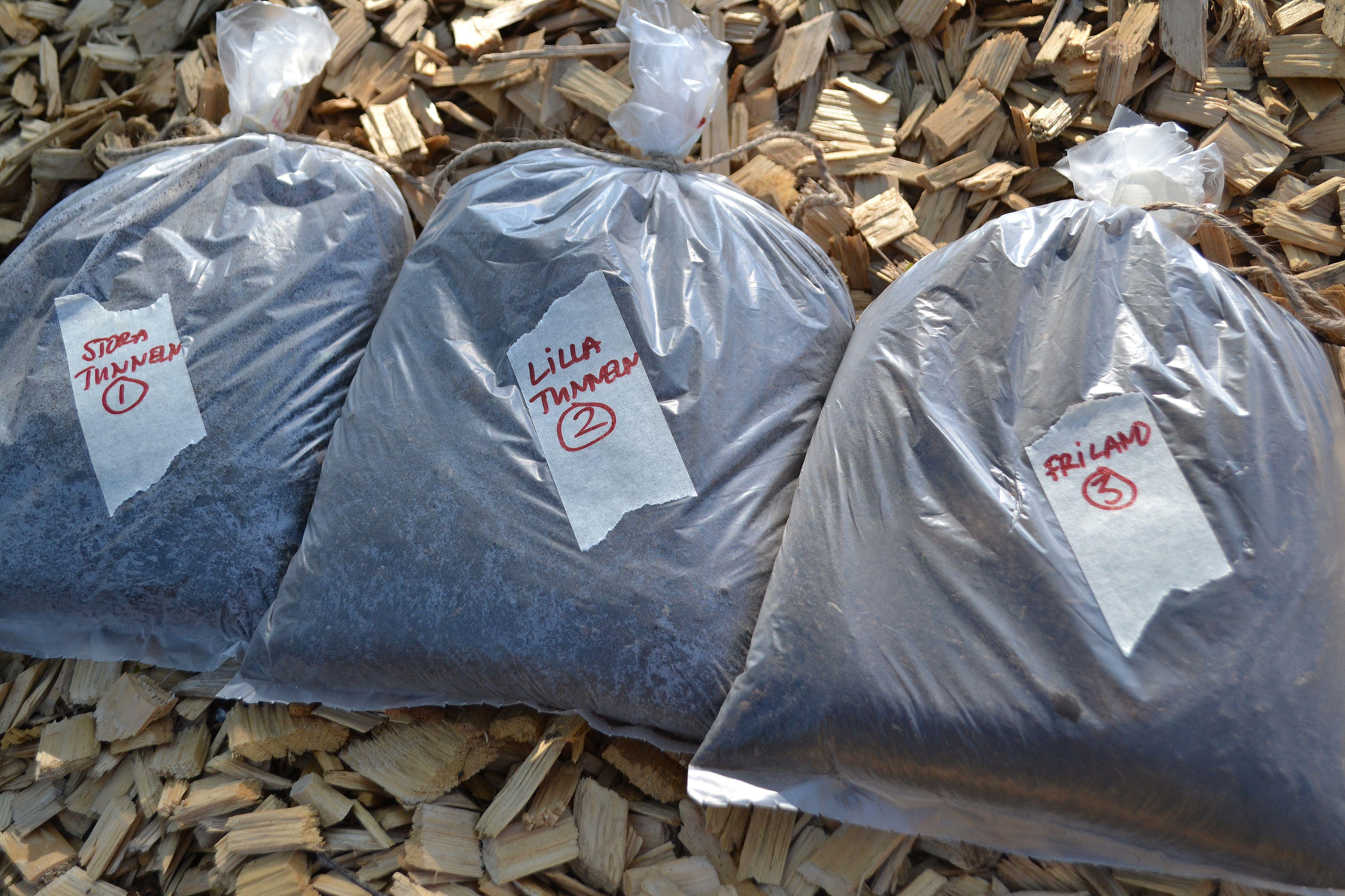 Tre fryspåsar med jord ligger på marken, med varsin tejpbit klistrad på med information.