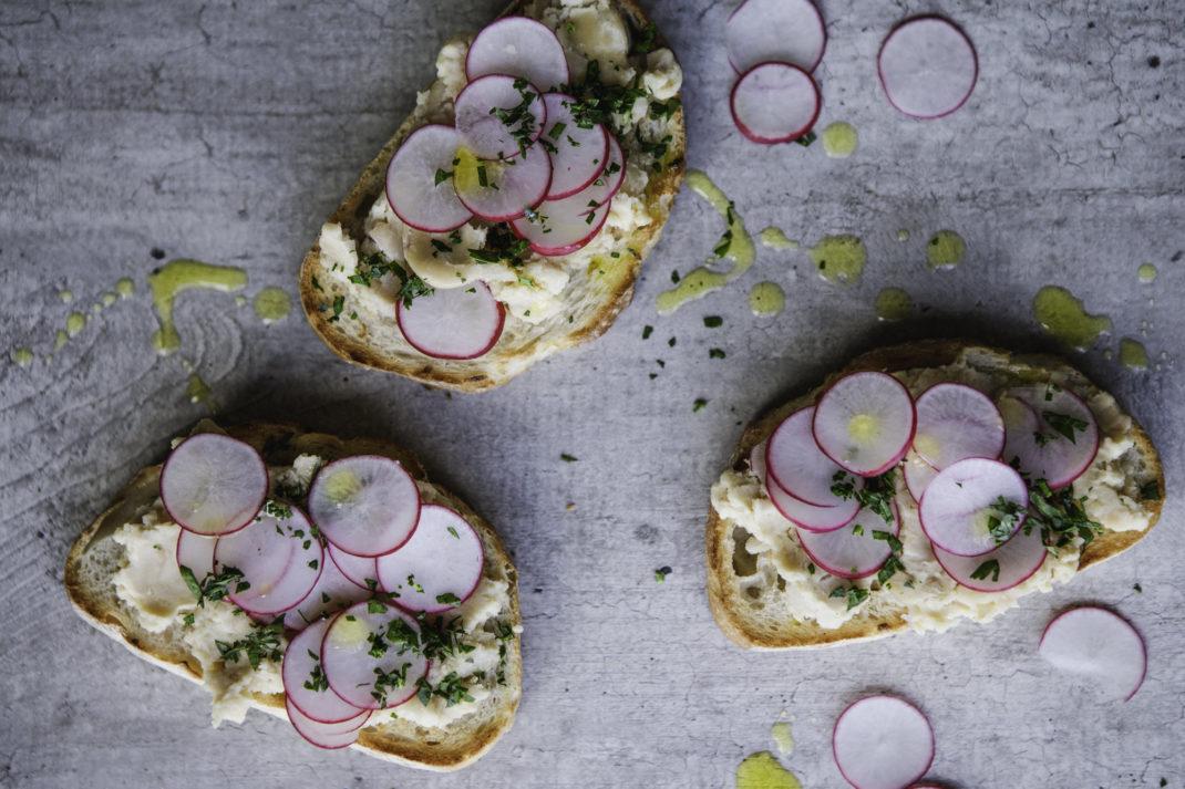 Tre smörgåsar med ljus bönröra och skivad rädisa. Refried beans