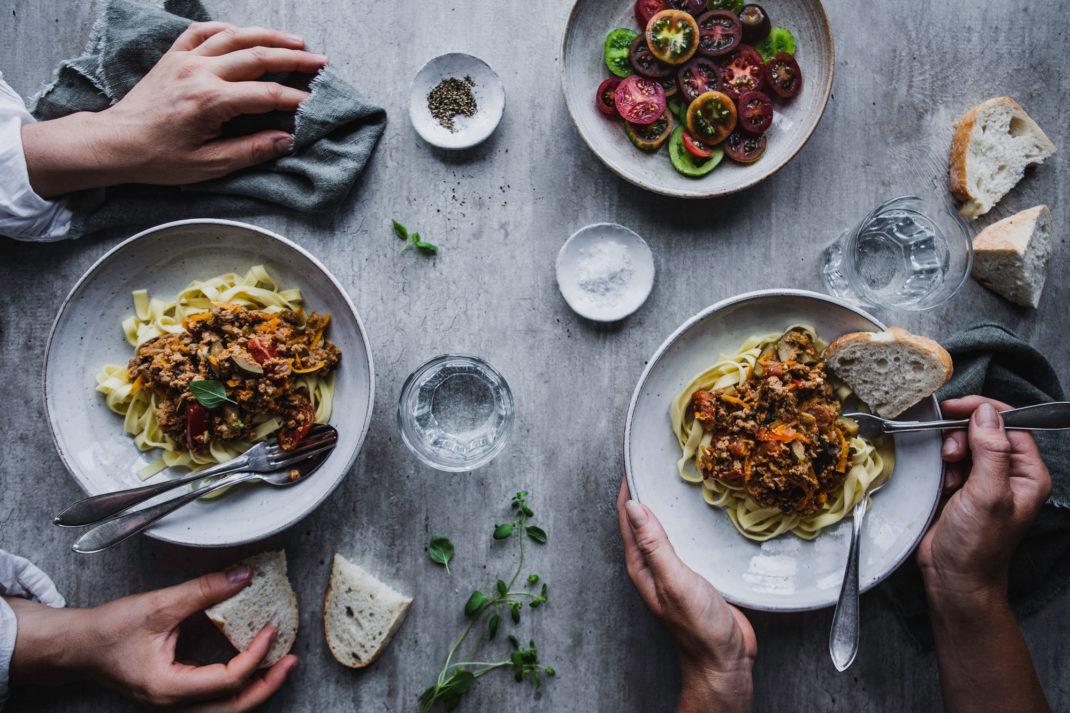 Ett bord sett uppifrån med två tallrikar pasta med köttfärssås, underbara tomater i olika färger och händer som tar för sig.