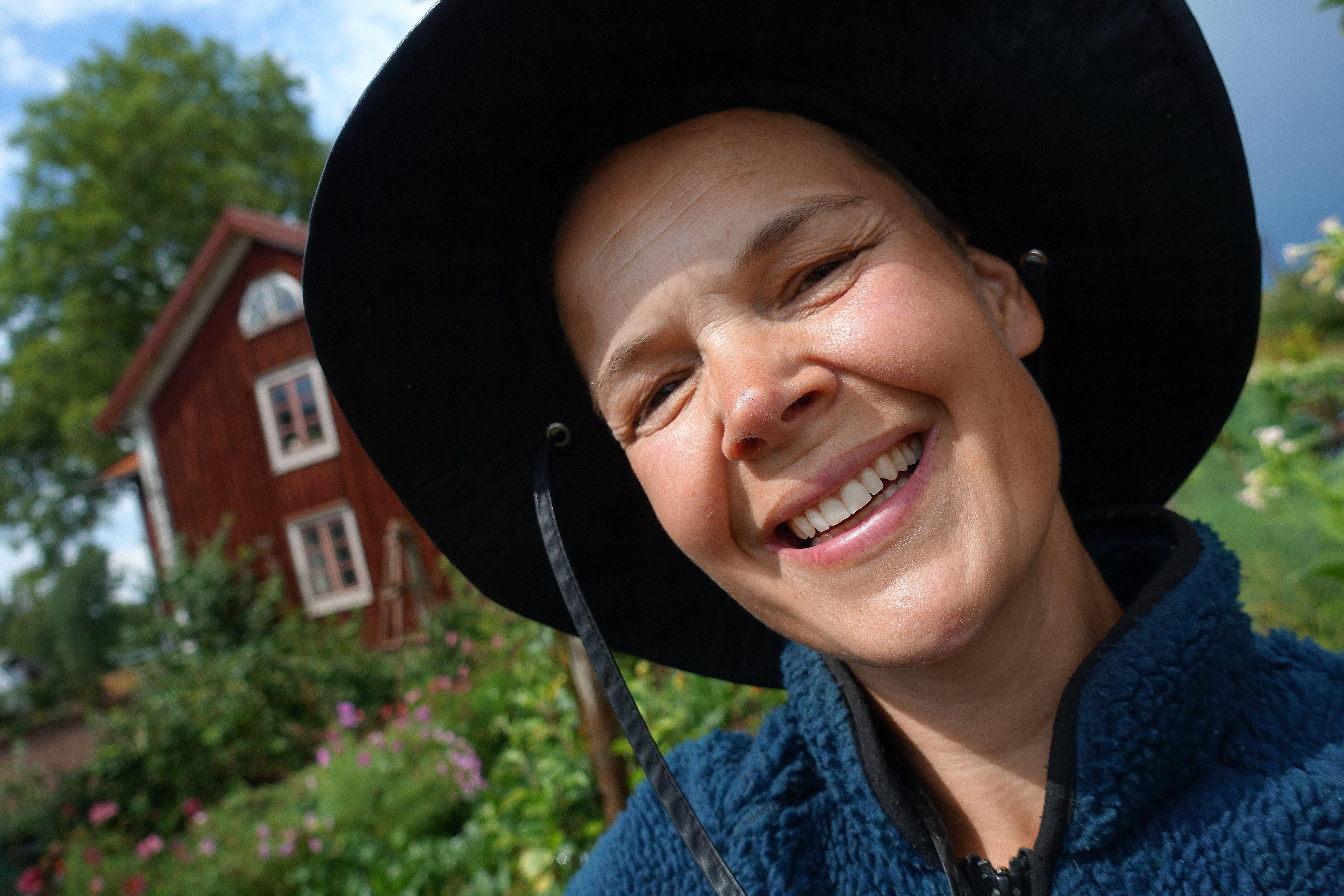 Bild på Sara med bostadshuset i bakgrunden. Sara har en svart hatt på sig. Summer sowing, Sara is wearing a black hat, house in the background.