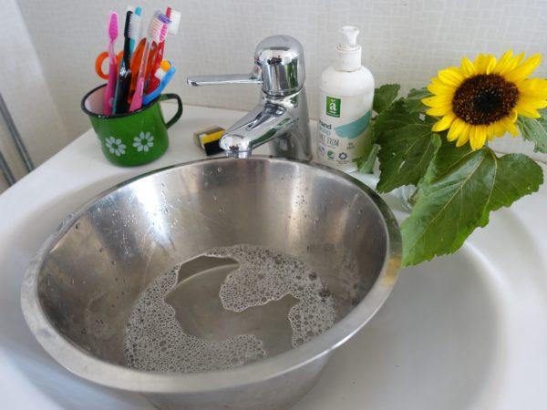 Ett handfat med en stor skål i rostfritt i, tandborstar i mugg på handfatet, en flaska tvål och en solros vid sidan av.