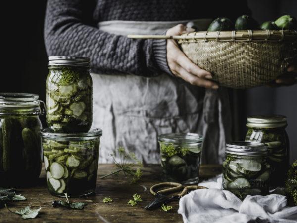 Fina glasburkar med gurka står på ett bord med massor av andra ingredienser. En kvinnas förkläde och händer syns i bild.