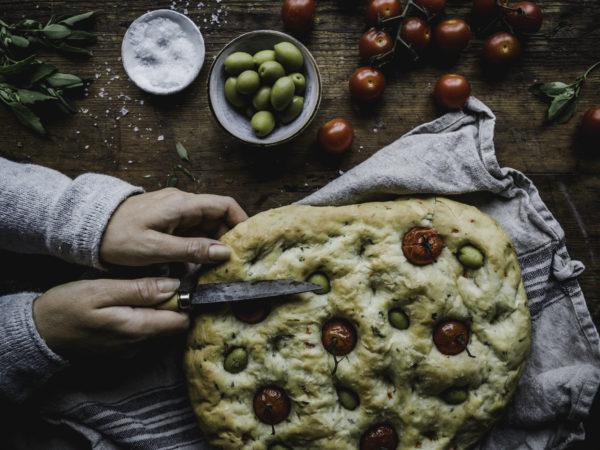 Focaccia, Två händer skär upp ett fantastiskt, platt bröd med tomater i.