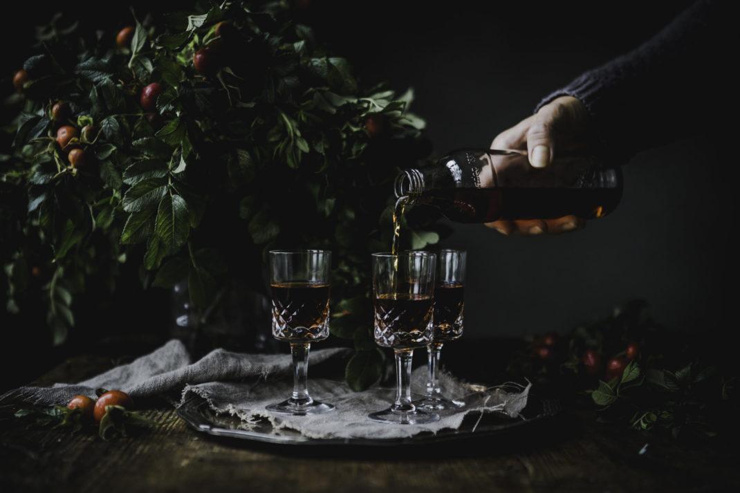 En hand häller upp en guldigt röd vätska i fina sherryglas bredvid en bukett med nypon.