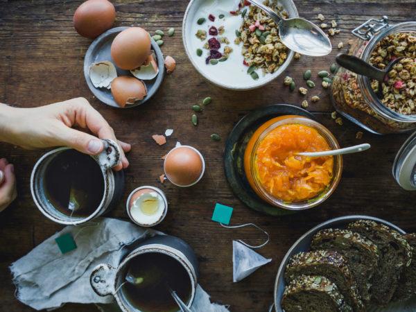 Ett helt frukostbord med mackor, ägg, müsli och morotsmarmelad.