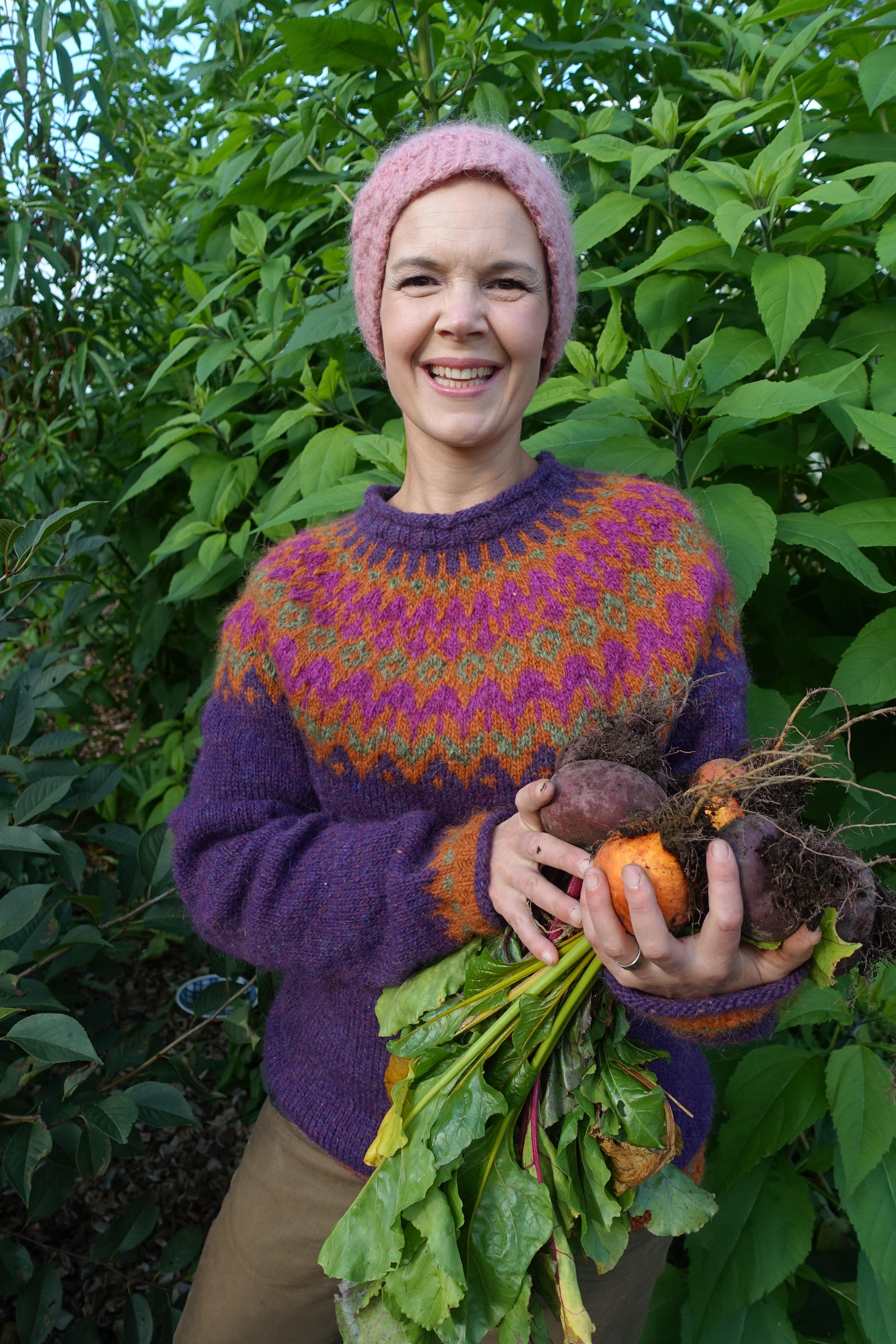 Sara står med färgranna betor i en vacker hemstickad tröja.