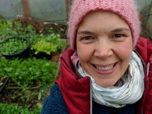 Sara Bäckmo sitter i mössa och vinterkläder i ett tunnelväxthus fullt av växter