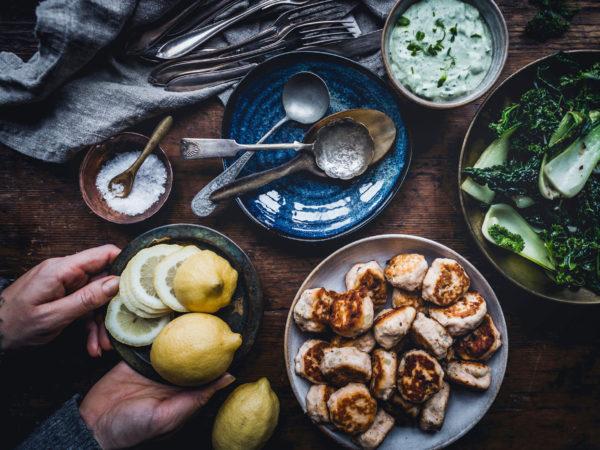 PÅ ett brunt bord står skålar med fiskbullar, citron, röror och kål.