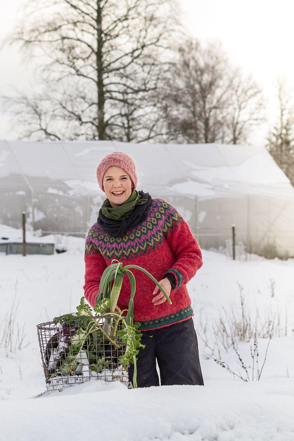 Sara Bäckmo står i en snöig trädgård med en korg ed grönsaker.