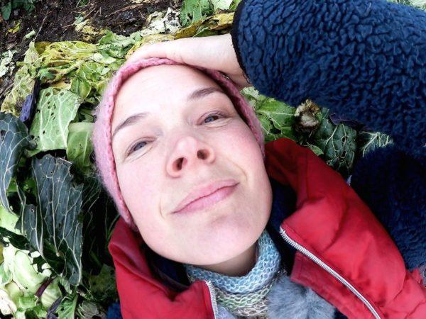 Sara Bäckmo ligger på en massa kålblad i landet.