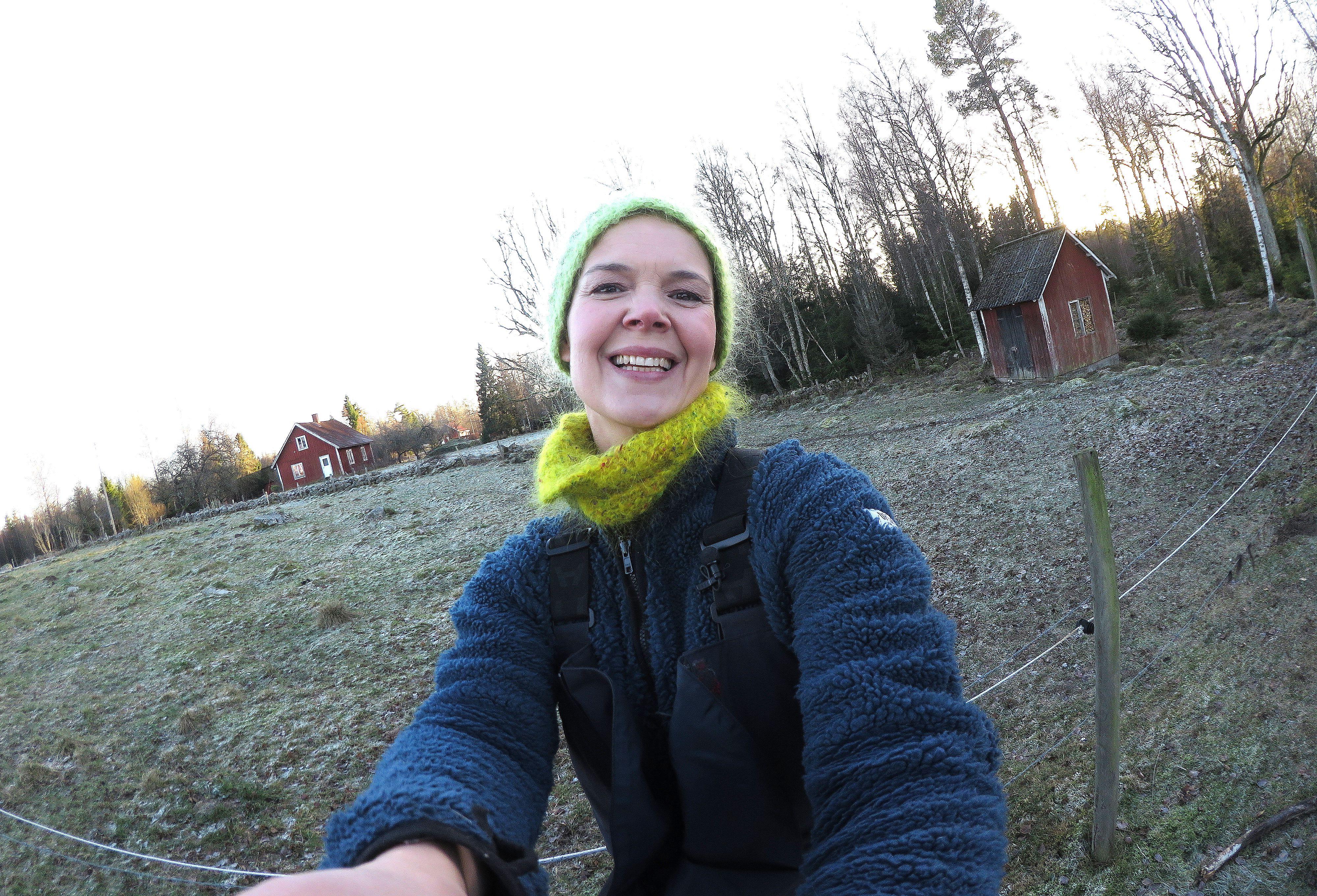 Sara Bäckmo står i trädgården med beteshagen bakom sig, vinter. #MyFavouriteVideo, Sara in the winter garden.