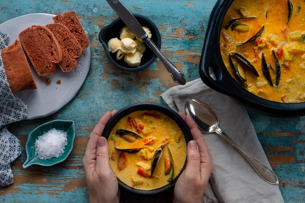 Guldgul fisksoppa i fina skålar mot ett avskavt blått trädbord. Fish stew with saffron and fennel.