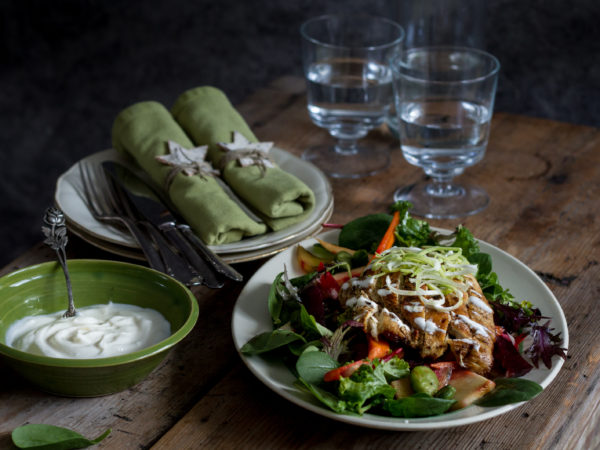 En vacker dukning med tygservetter, vackra glas och en vintrig sallad med rotsaker, kyckling och bönor.