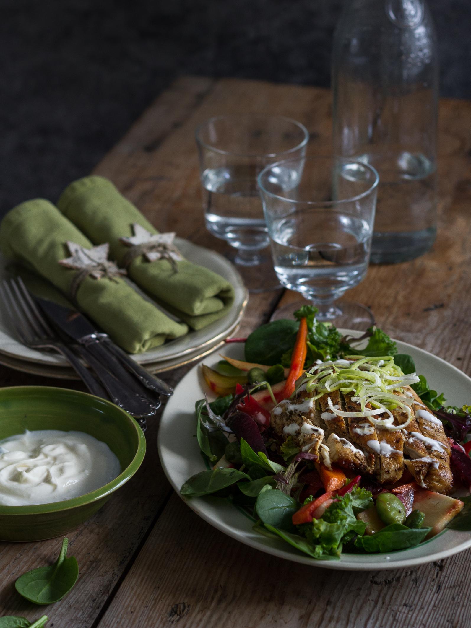 En vacker dukning med tygservetter, vackra glas och en vintrig sallad med rotsaker, kyckling och bönor. Root vegetable salad, table with beautiful glasses.