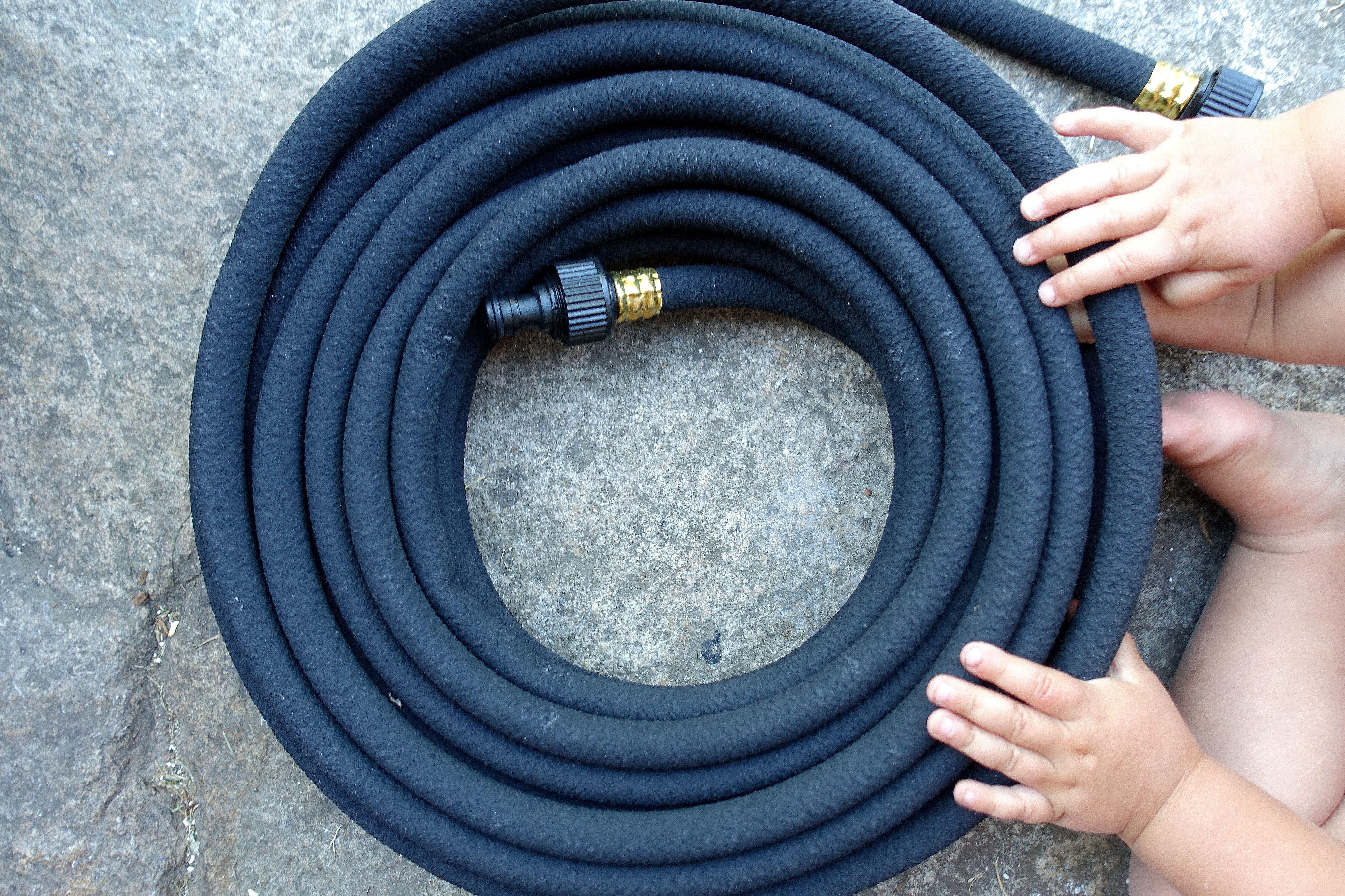 En ihoprullad svart slang. Soaker hose, black.