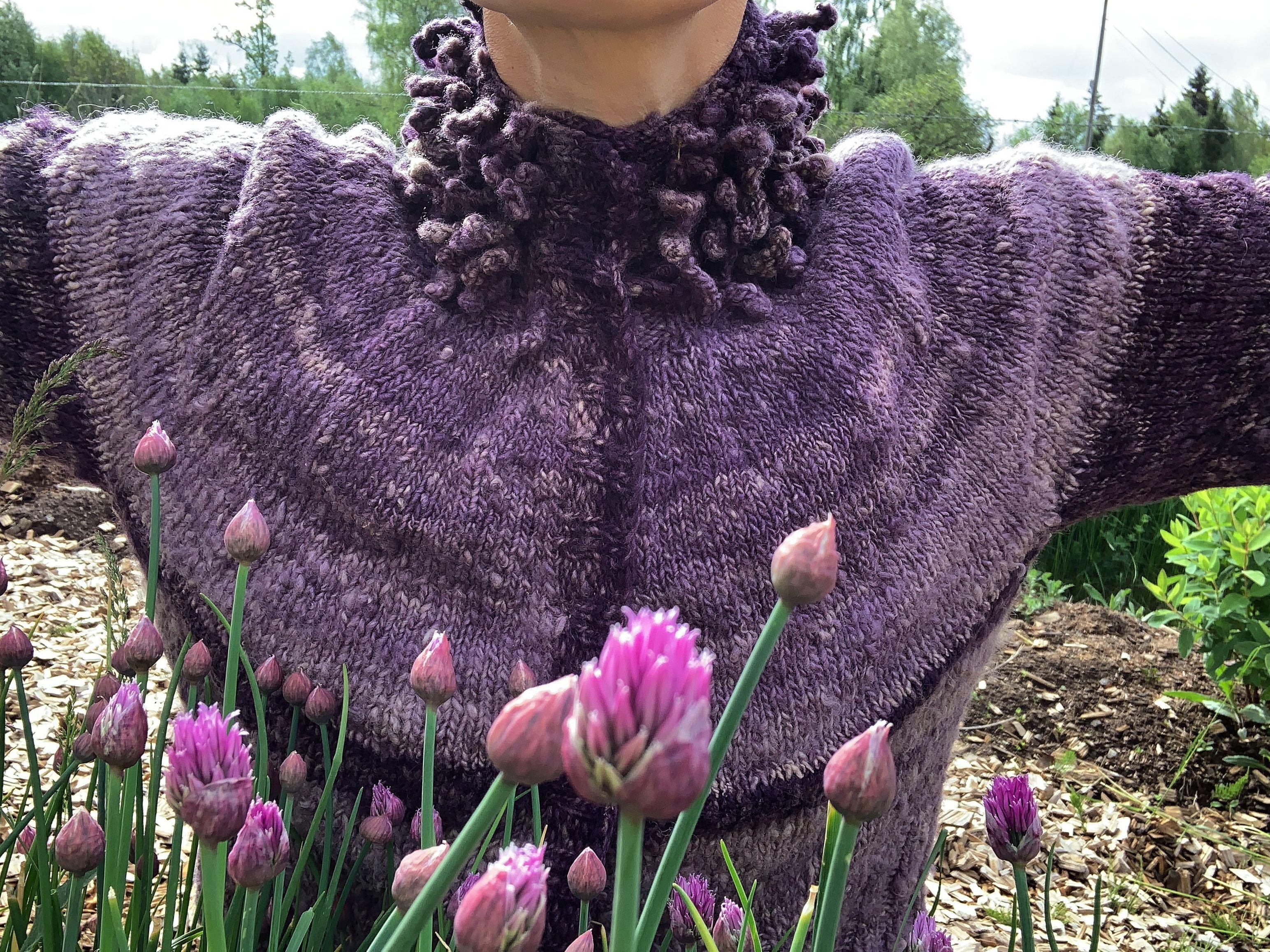 Sara med utfällda armar i lila kofta och gräslöken som blommar i förgrunden. Puff sleeve cardigan, chives in the foreground.