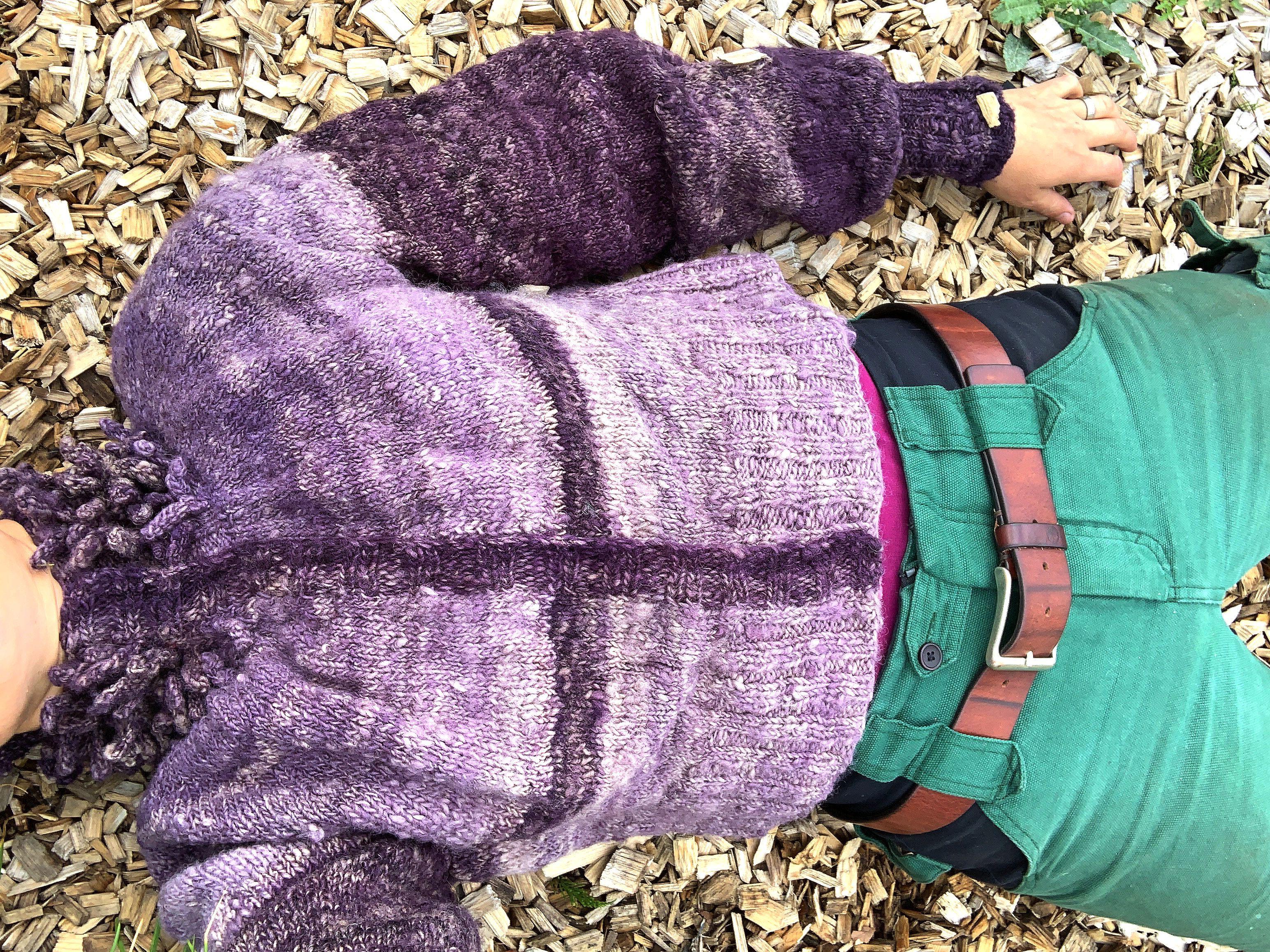 Sara ligger på träflis och hela tröjan syns. My puff sleeve cardigan.