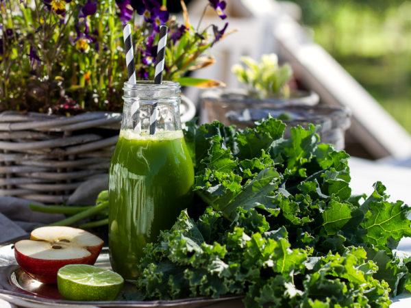 Grönkålsjuice i glaskflaska med randigt sugrör.