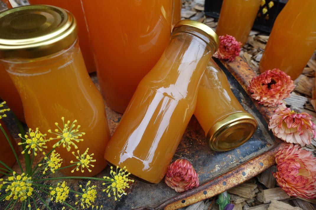 Små flaskor med varmt orange must ligger och står på träflis utomhus.