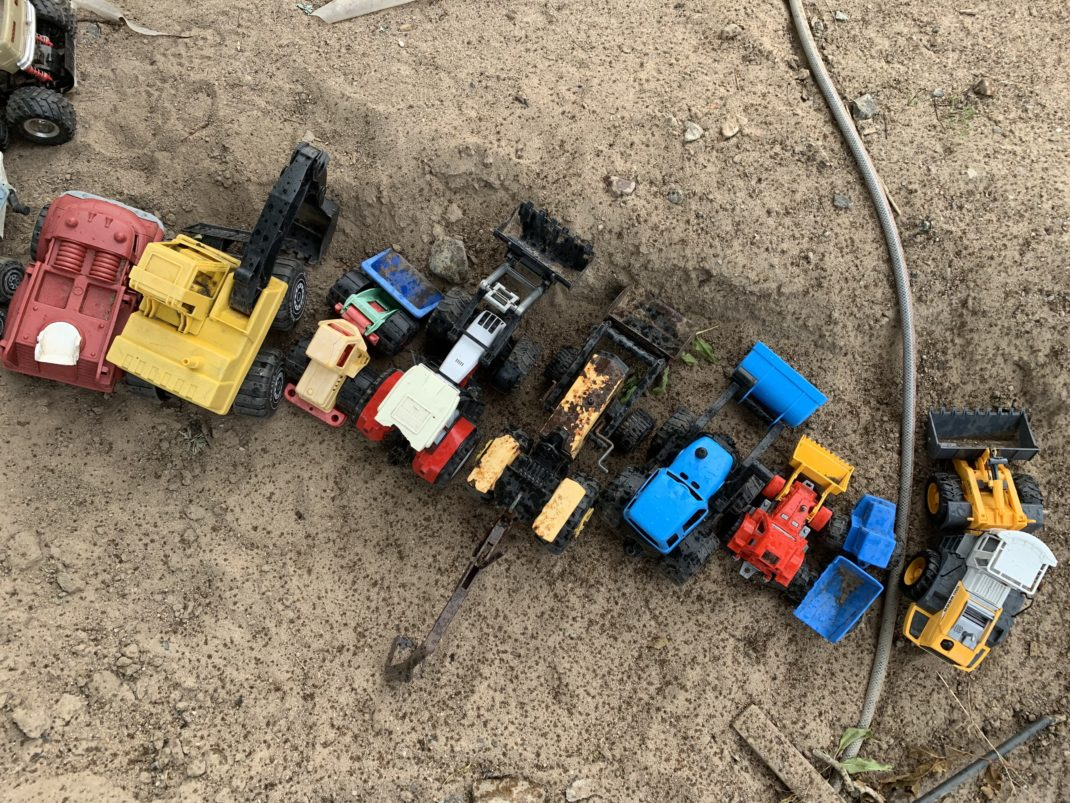 Leksaksbilar uppställda på rad i sandlådan.