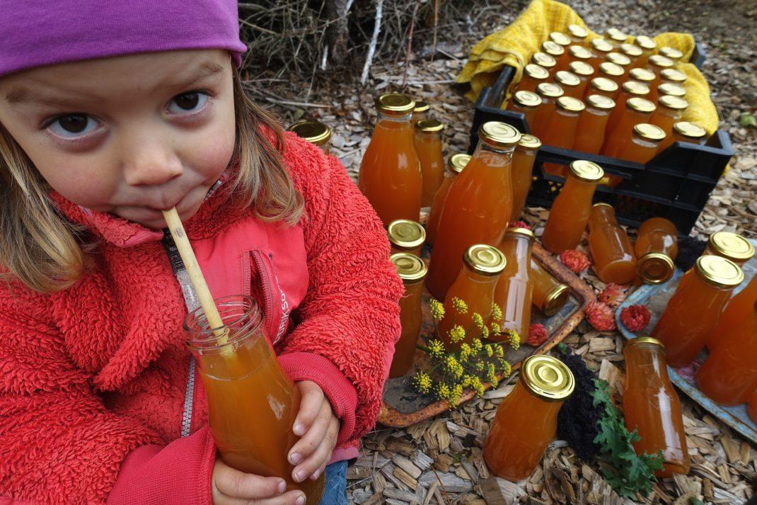 Ett litet barn i färgglada kläder dricker must ur en flaska med sugrör.