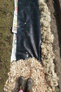 Bild tagen ovanifrån där tidningar, markduk och träflis ligger i olika lager.