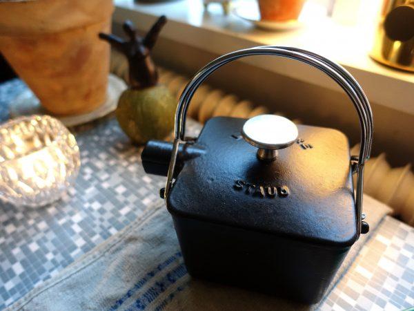 Bild från ett köksbord med tända ljus och en svart tekanna i järn.