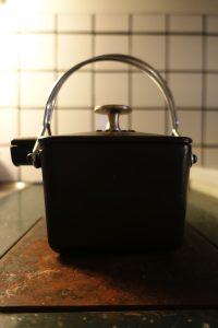 Siluetten av en fyrkantig svart tekanna på ovansidan av en kökspanna.