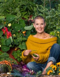 Sara i solrosgul tröja mitt i köksträdgårdens mylla