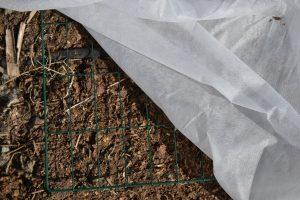 En tunn fiberduk över jord med kompostgaller på.