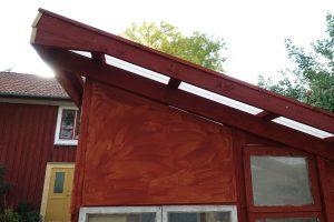 Rödmålad träbit på växthuset.