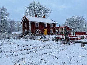 Ett rött trähus med växthus och köksträdgård framför, allt insvept i ett vintertäcke.