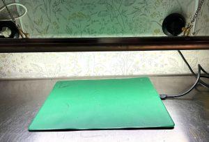 En platt grön matta på bänk av rostfritt stål.