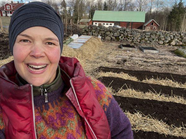 Glad Sara framför odlingsbäddar med svart jord.